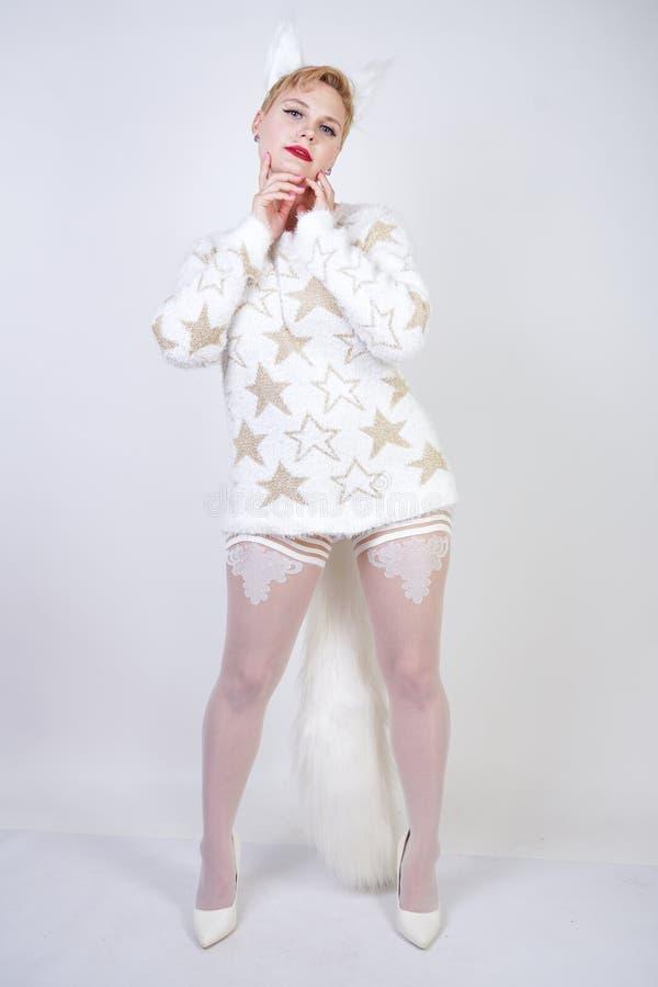 Hübsches nettes nettes Mädchen mit dem blonden kurzen Haar und tragender weißer Strickjacke des curvy Plusgrößenkörpers mit golde lizenzfreies stockfoto
