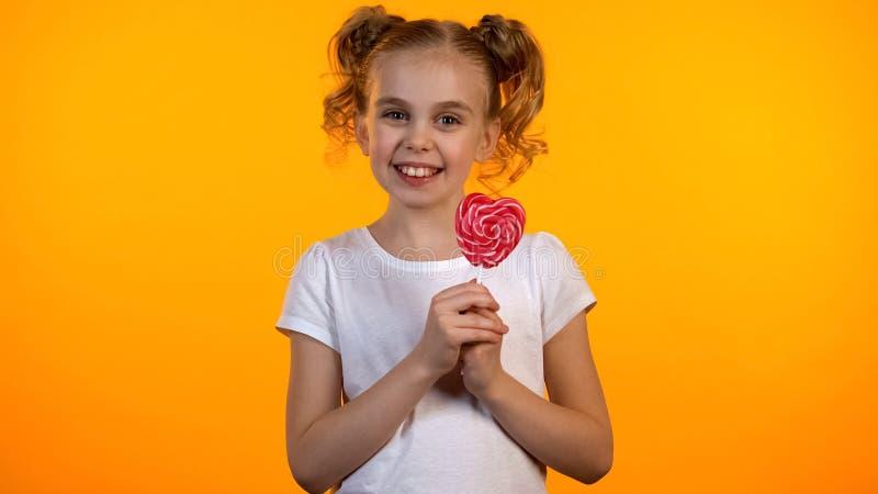 Hübsches Süßigkeitsmädchen, das Herz-förmigen Lutscher hält und zur Kamera, Glück lächelt stockfotos