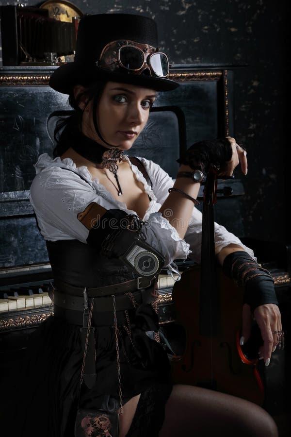 Hübsches steampunk Mädchen, das nahe bei dem Klavier sitzt stockbild