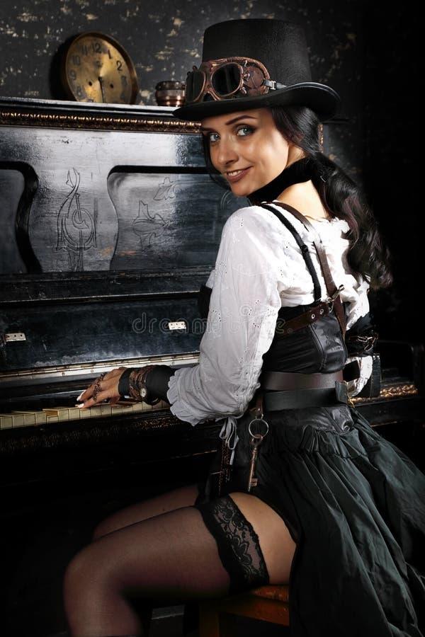 Hübsches steampunk Mädchen, welches das Klavier spielt stockbild