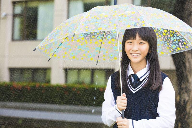 Hübsches Studentenmädchen, das Regenschirm im Regen hält stockfotos