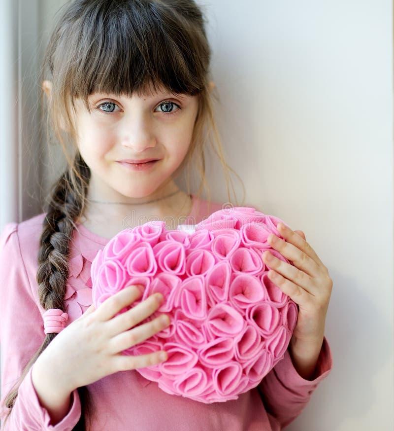 Hübsches toddelr Mädchen, das rosafarbenes Inneres hängend anhält stockbild