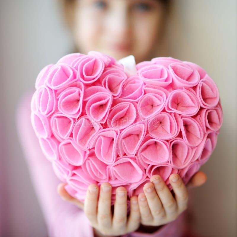Hübsches toddelr Mädchen, das rosafarbenes Inneres hängend anhält lizenzfreies stockfoto