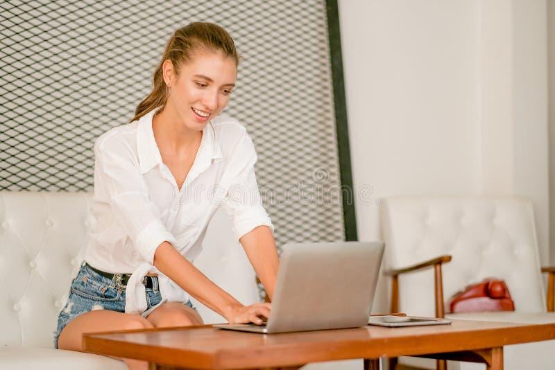 Hübsches und schönes Mädchen sitzen auf Sofa und Gebrauchslaptop auf Tabelle für das Arbeiten und schauen mit Konzept von zu Haus lizenzfreie stockbilder