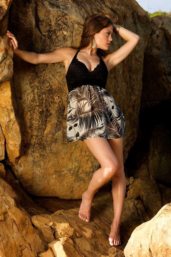 Hübsches weibliches Baumuster, das auf den Felsen steht stockfotos