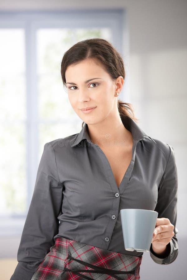 Hübsches weibliches mit Teebecher in der Hand lächeln stockfotografie