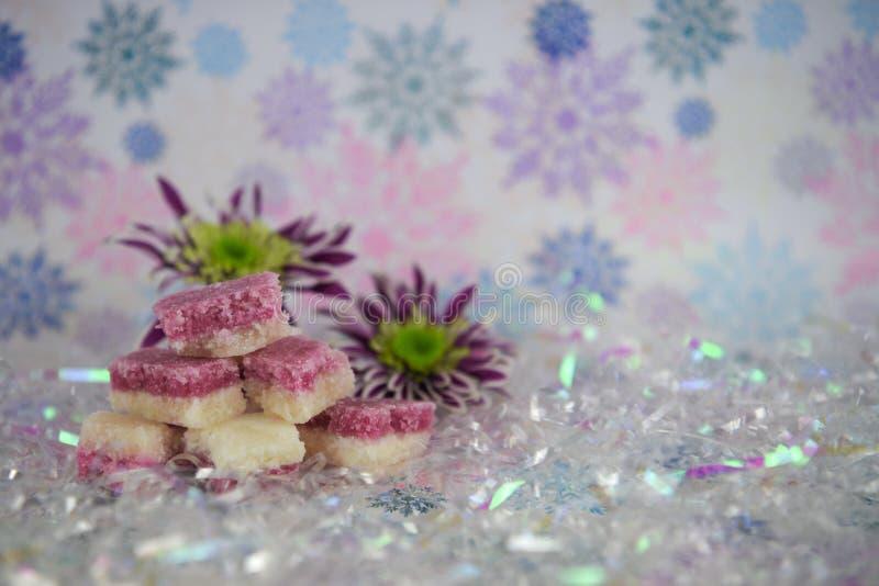 Hübsches Weihnachtslebensmittel-Fotografiebild von englischen altmodischen Kokosnusseisbonbons mit Winterblumen und Schneeflocken lizenzfreie stockfotos