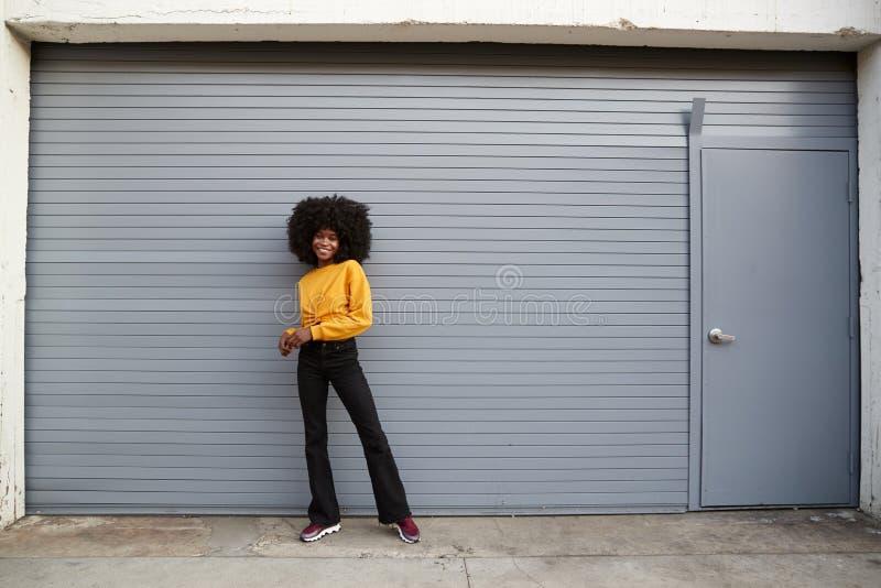 Hüften-junge Afroamerikanerfrauenstellung gegen die grauen Sicherheitsfensterläden, die zur Kamera, in voller Länge lächeln stockfoto