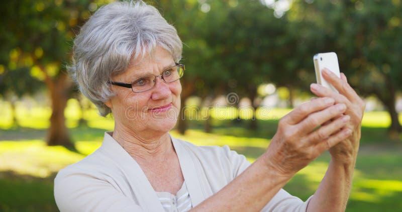 Hüftengroßmutter, die selfies am Park nimmt stockfotos