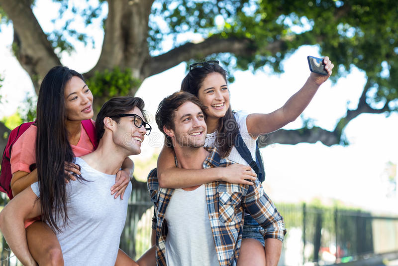 Hüftenmänner, die piggyback ihren Freundinnen geben und selfie nehmen stockbild