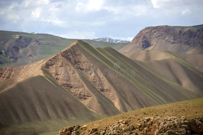 Hügel bedeckt mit jungem Gras gegen den Himmel und die Schnee-mit einer Kappe bedeckten Bergspitzen Reise kyrgyzstan stockfotos
