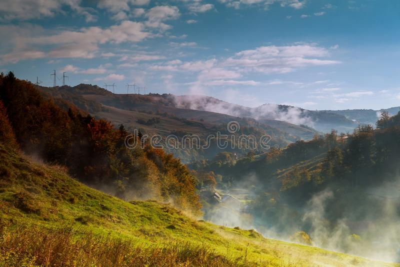 Hügelige Landschaft des Herbstes umfasst in verweilendem Nebelnebel mit warmem Morgenlicht stockbilder