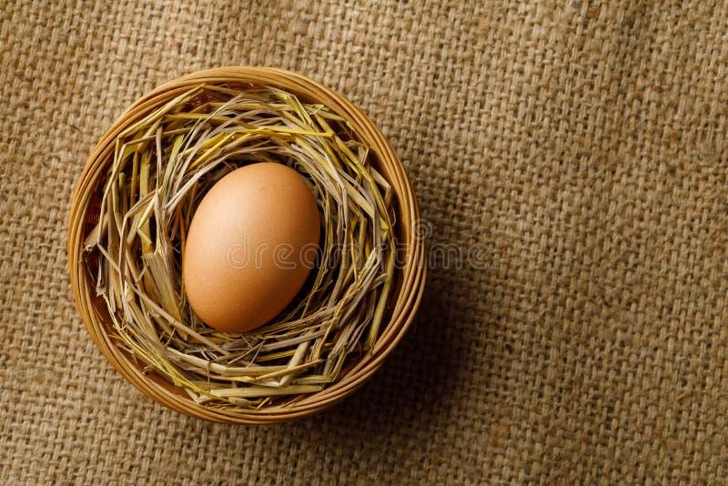 Hühner- oder Hühnerei auf Stroh im Weidenkorb auf Sackleinen stockfotos