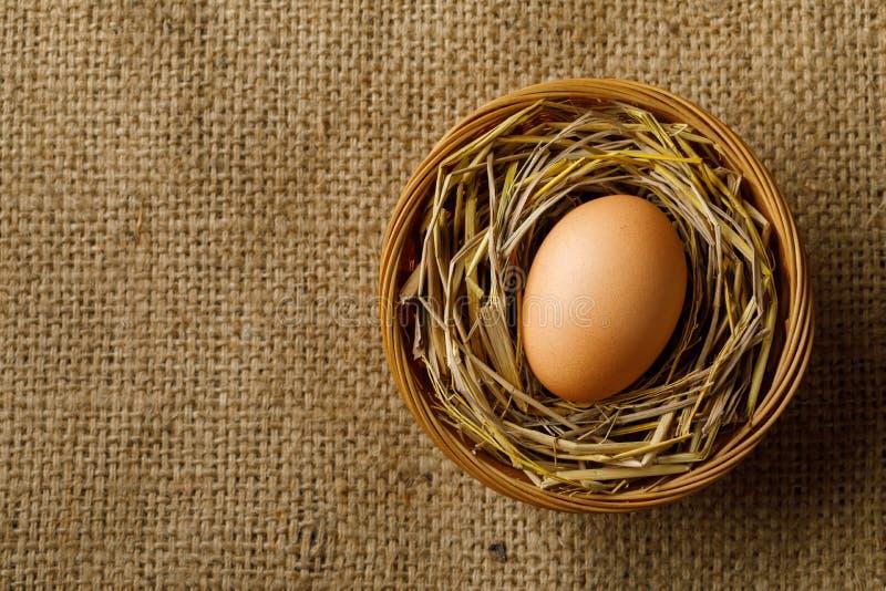 Hühner- oder Hühnerei auf Stroh im Weidenkorb auf Sackleinen lizenzfreies stockfoto