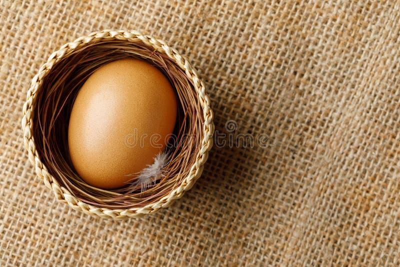Hühner- oder Hühnerei im Weidenkorb auf Sackleinen lizenzfreie stockbilder