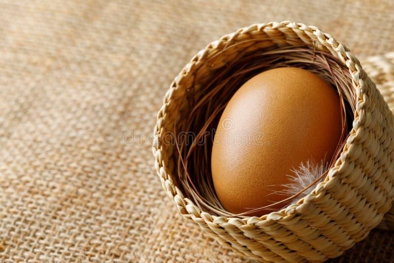 Hühner- oder Hühnerei im Weidenkorb auf Sackleinen stockfotos