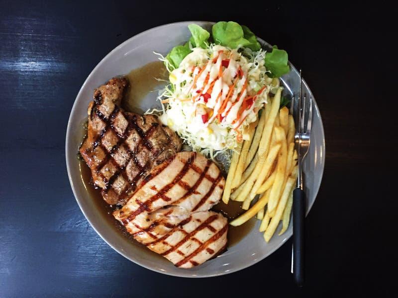 Hühner- und Schweinefleischsteak mit Soße des schwarzen Pfeffers lizenzfreies stockfoto