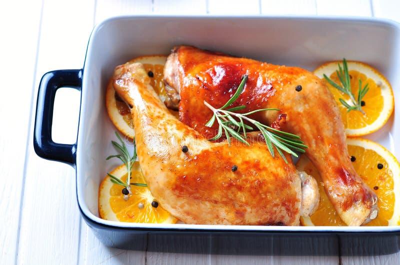 Hühnerbein briet mit Olivenöl, Balsamico-Essig und Sojasoße mit orange Scheiben, Rosmarin, Pfeffer und Seesalz lizenzfreie stockbilder