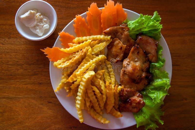 Hühnerbrust mit Pommes-Frites und Salat auf weißer Platte Gebratenes Hühnerdraufsichtfoto auf Holztisch lizenzfreie stockfotografie