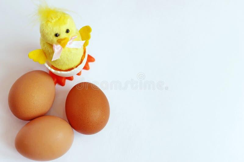 H?hnereien sind nahe bei einem gelben Huhn des Spielzeugs braun Fr?hliche Ostern stockbilder
