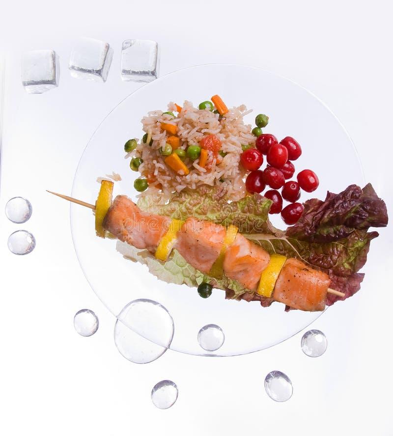 Hühnerkebab mit Reis und Gemüse auf einem weißen Hintergrund auf einem transparenten Platte decoratet mit Glassteinen stockbild