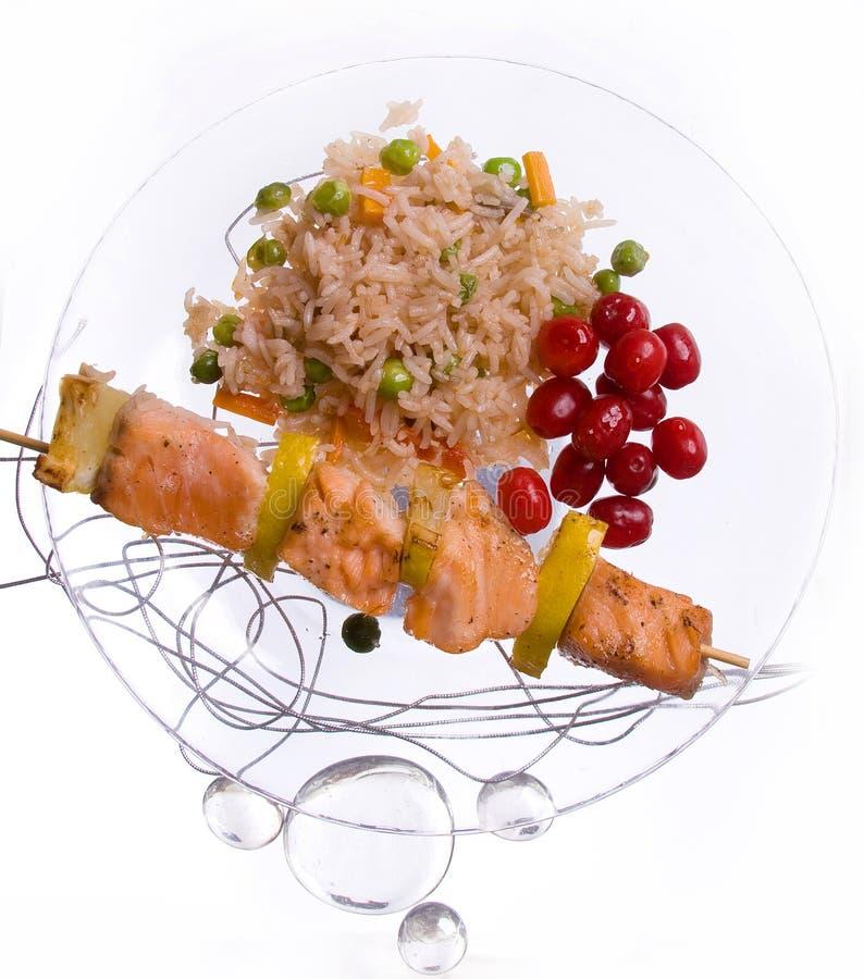 Hühnerkebab mit Reis und Gemüse auf einem weißen Hintergrund auf einem transparenten Platte decoratet mit Glassteinen lizenzfreie stockfotografie