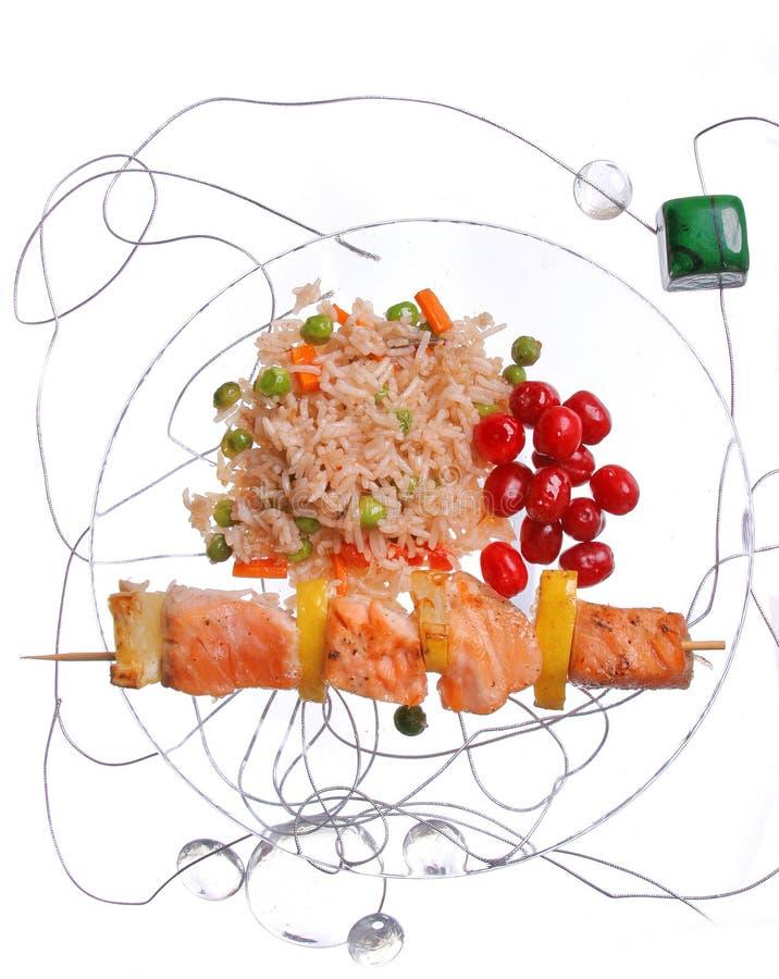 Hühnerkebab mit Reis und Gemüse auf einem weißen Hintergrund auf einem transparenten Platte decoratet mit Glassteinen stockfotografie