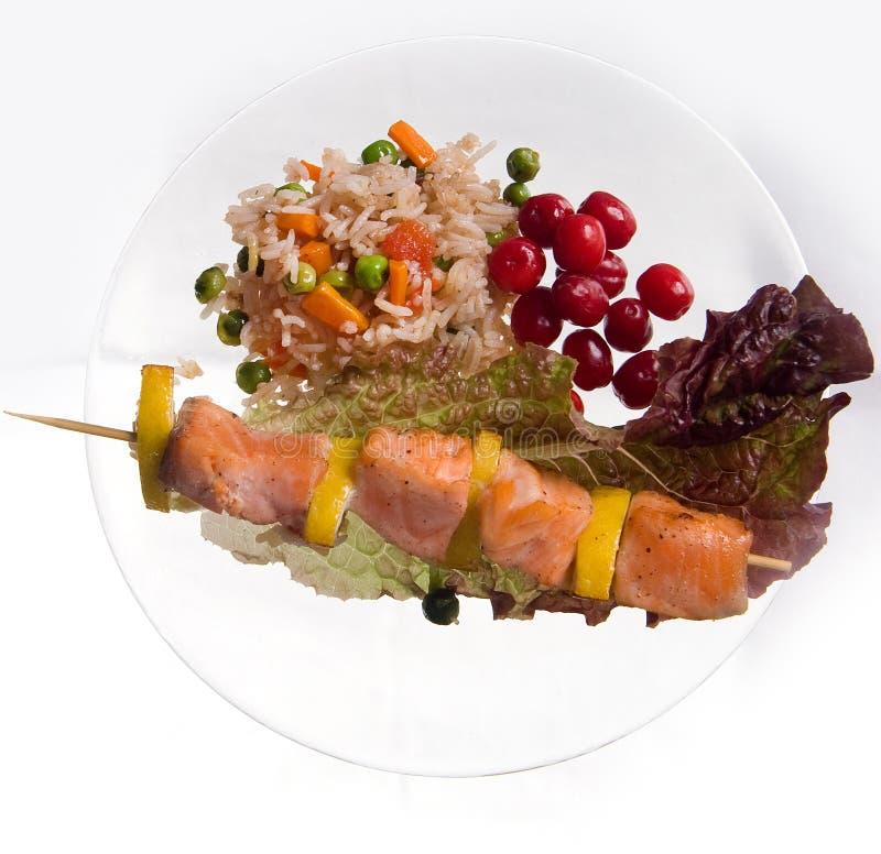 Hühnerkebab mit Reis und Gemüse auf einem weißen Hintergrund auf einem transparenten Platte decoratet mit Glassteinen lizenzfreie stockfotos