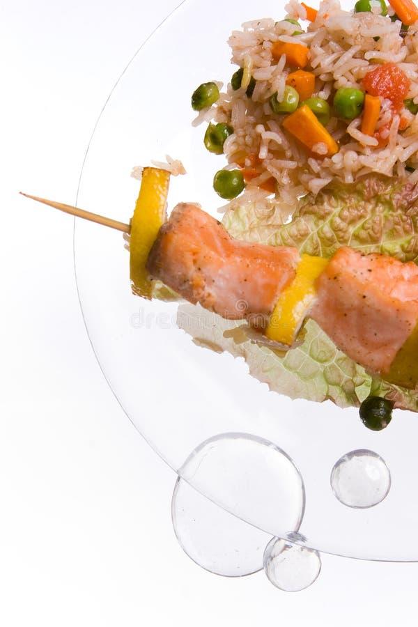 Hühnerkebab mit Reis und Gemüse auf einem weißen Hintergrund auf einem transparenten Platte decoratet mit Glassteinen lizenzfreies stockbild