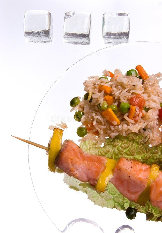 Hühnerkebab mit Reis und Gemüse auf einem weißen Hintergrund auf einem transparenten Platte decoratet mit Glassteinen lizenzfreie stockbilder