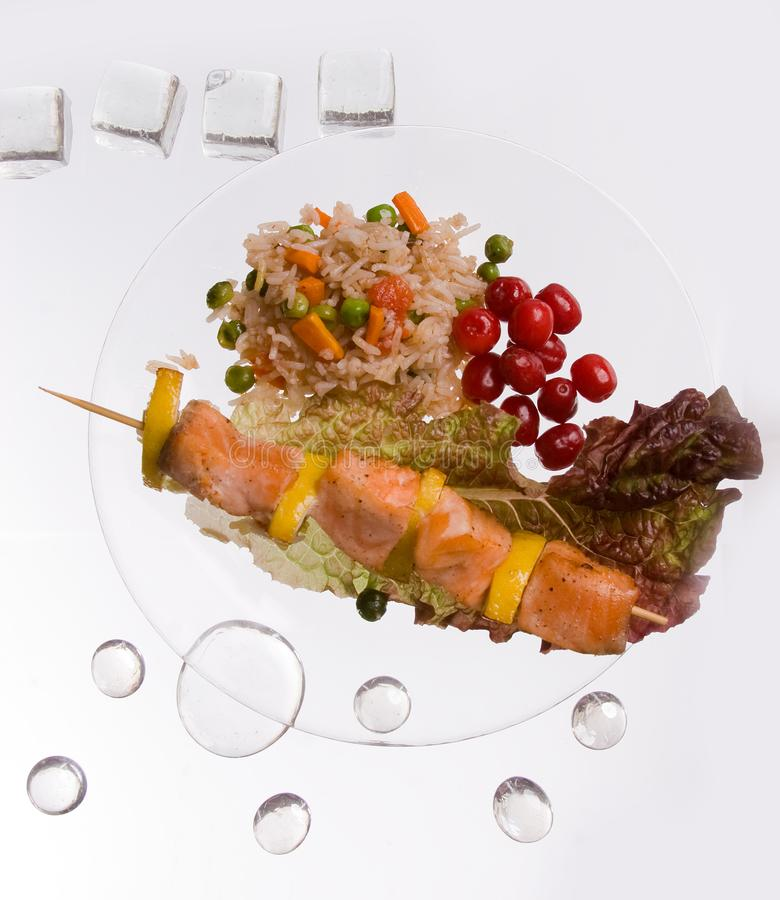 Hühnerkebab mit Reis und Gemüse auf einem weißen Hintergrund auf einem transparenten Platte decoratet mit Glassteinen stockfoto