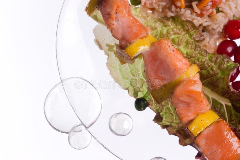 Hühnerkebab mit Reis und Gemüse auf einem weißen Hintergrund auf einem transparenten Platte decoratet mit Glassteinen stockbilder