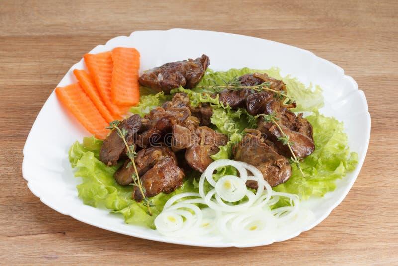 Hühnerleber kochte mit Zwiebeln, Kopfsalat und Gewürzen lizenzfreie stockfotos