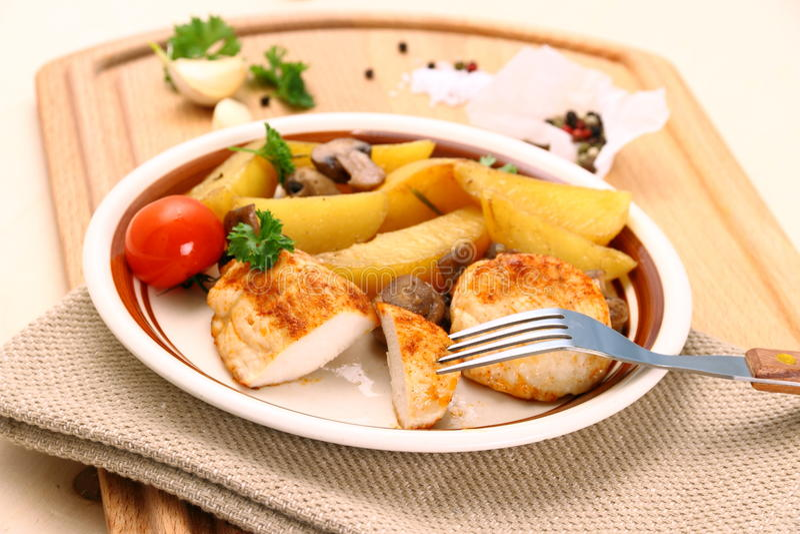 Hühnerleiste mit Rosmarinkartoffeln und -pilz stockbild