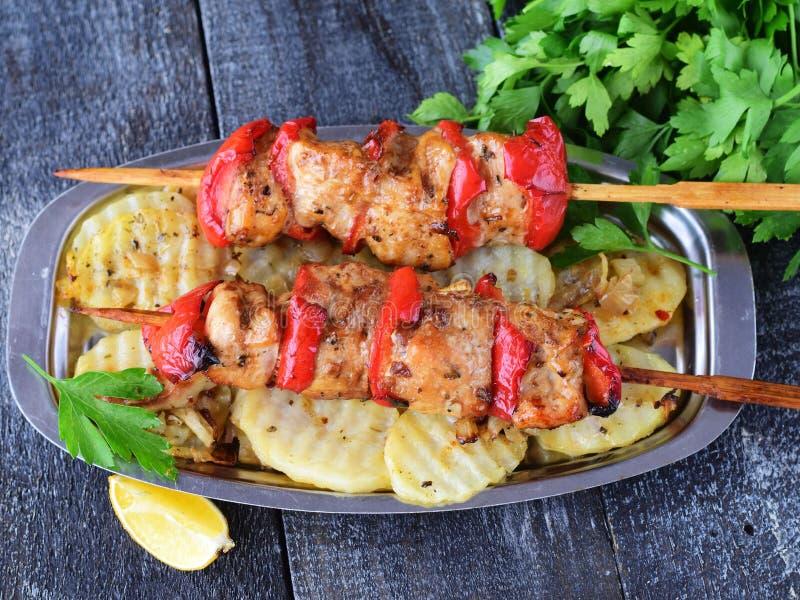 Hühnerleiste mit süßem Paprika grillte mit gebratener Kartoffel auf einer Metallplatte auf einem hölzernen Hintergrund Gesundes E stockfotografie