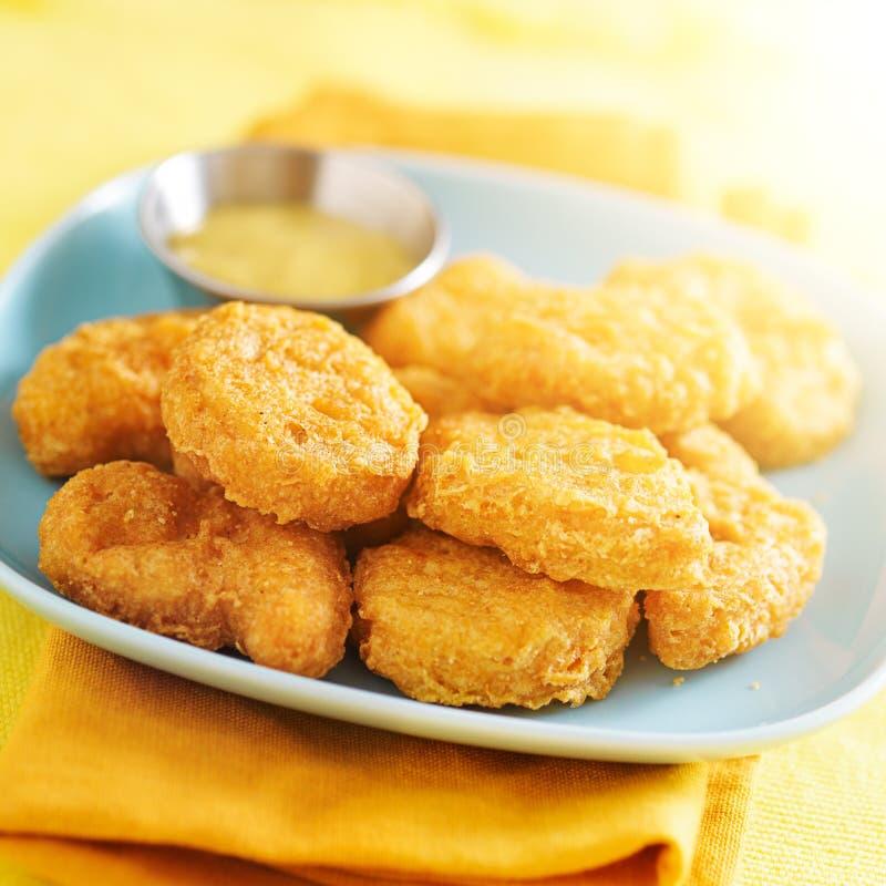 Hühnernuggets auf gelbem Stoff lizenzfreie stockfotos