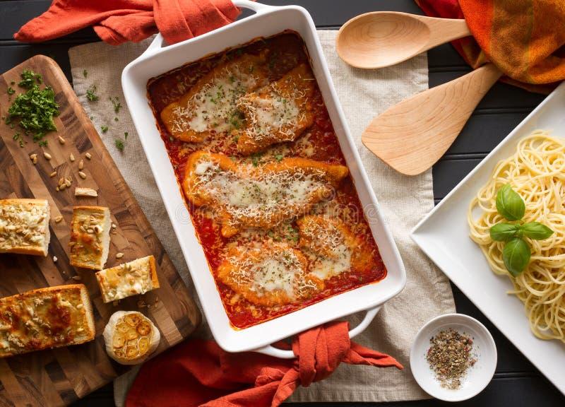 Hühnerparmesankäse-Abendessen mit Teigwaren und frischem Knoblauch-Brot lizenzfreie stockfotos