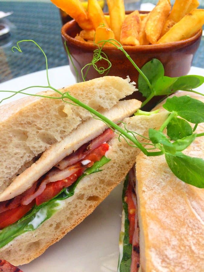Hühnerspeckkopfsalat und Tomatensandwich in ciabatta Brot mit goldenen Chips stockfoto