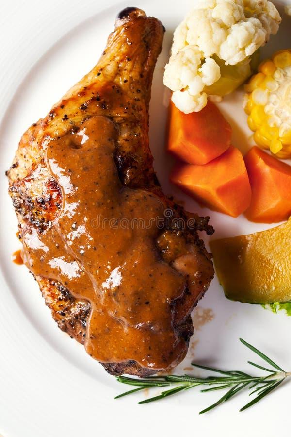 Hühnersteak mit Soße und Gemüse des schwarzen Pfeffers lizenzfreie stockfotografie