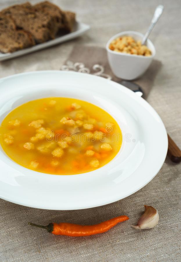 Hühnersuppe mit Gemüse in der weißen Schüssel mit Croutoncrackern und Brot pfeffern auf Tischdecke lizenzfreie stockbilder