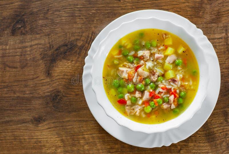 Hühnersuppe mit Reis und Gemüse in der Schüssel auf Holztisch lizenzfreie stockfotografie