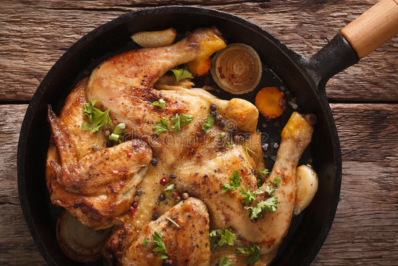 Hühnertabaknahaufnahme in einer Bratpfanne auf dem Tisch horizonta stockbild