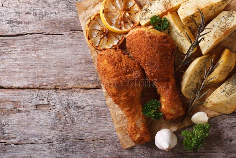 Hühnertrommelstöcke in den Brotkrumen mit Kartoffeln, Draufsicht stockbild