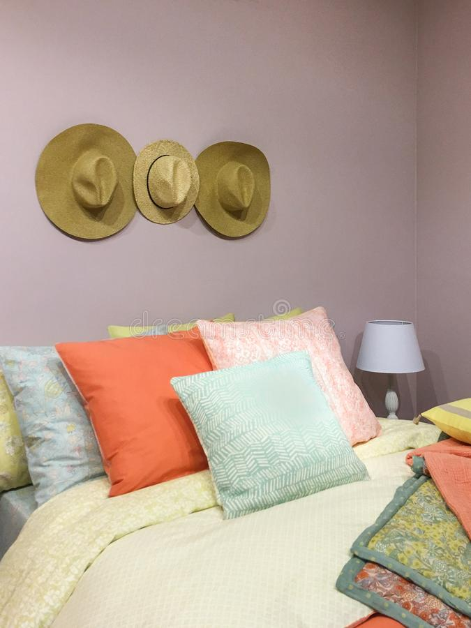 Hüte auf der rosa Wand nahe bei dem Bett und den Kissen stockbilder