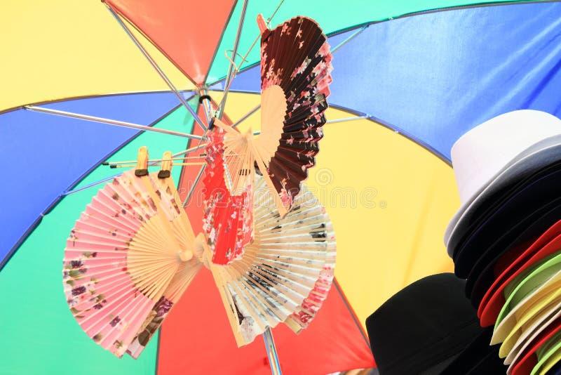 Hüte und Fans unter Regenschirm stockbild