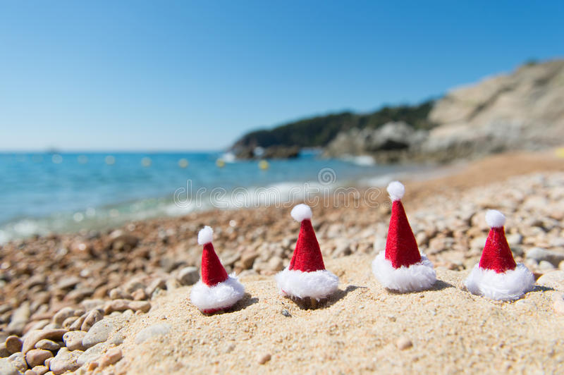 Hüte von Santa Claus am Strand lizenzfreie stockfotografie