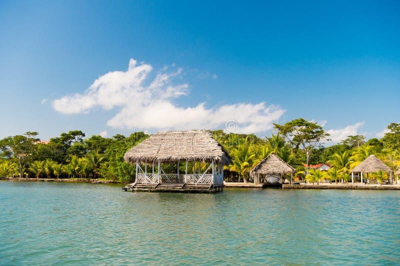 Hütten auf Seeufer in Guatemala, santo tomas Häuser des Holzes und des Grases auf tropischem Strand auf sonnigem blauem Himmel So lizenzfreies stockfoto