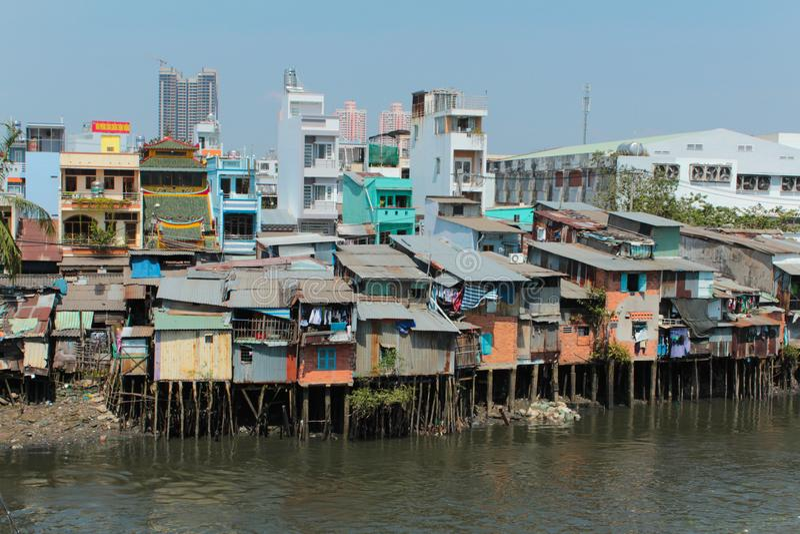 Hütten des armen Viertels auf Stelzen am Flussufer in Ho Chi Minh stockbild
