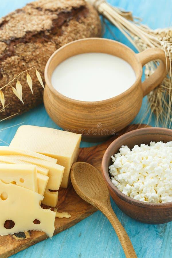Hüttenkäse, Milch, Brot und Käse auf einem hölzernen Hintergrund stockbild