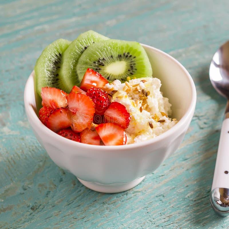 Hüttenkäse mit Erdbeeren, Kiwi, Honig und Leinsamen - gesundes Frühstück in einer weißen Schüssel lizenzfreie stockfotos